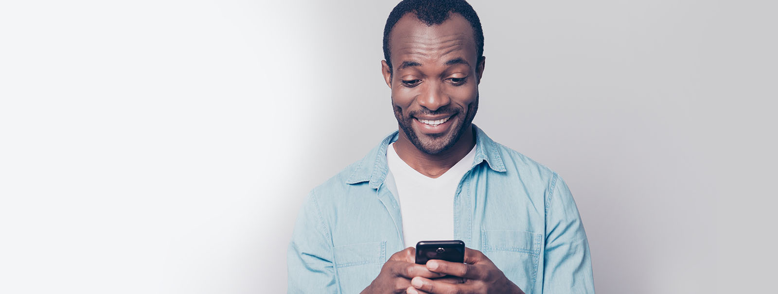 Smiling man looking at mobile phone.